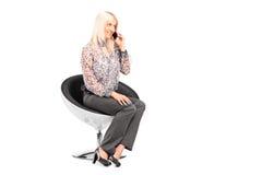 Junge Frau, die auf einem Stuhl sitzt Stockfotos