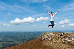 Junge Frau, die auf einen Hintergrund von Bergen springt Stockfoto