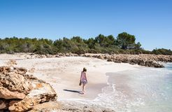 Junge Frau, die auf einen idyllischen weißen Sandstrand auf der Mittelmeerküste geht lizenzfreie stockbilder