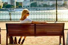 Junge Frau, die auf einer Bank auf dem Flussufer stationiert Lizenzfreie Stockbilder