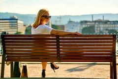 Junge Frau, die auf einer Bank auf dem Flussufer stationiert Lizenzfreie Stockfotografie
