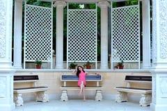 Junge Frau, die auf einer Bank in einem schönen Park stillsteht stockfotos