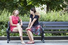 Junge Frau, die auf einer Bank im Park stillsteht Stockbild