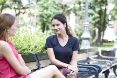 Junge Frau, die auf einer Bank im Park stillsteht Lizenzfreies Stockfoto