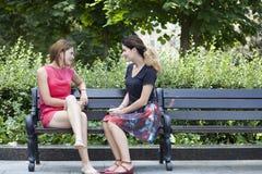 Junge Frau, die auf einer Bank im Park stillsteht Stockbilder