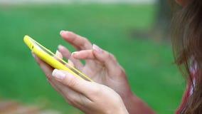 Junge Frau, die auf einer Bank im Sommerpark mit einem Smartphone sitzt stock footage