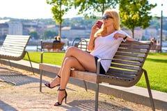 Junge Frau, die auf einer Bank mit einem Kaffee stationiert Stockbild