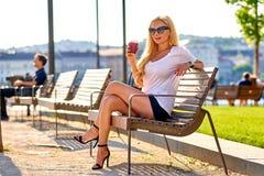 Junge Frau, die auf einer Bank mit einem Kaffee stationiert Lizenzfreie Stockfotografie