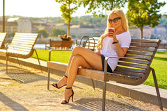 Junge Frau, die auf einer Bank mit einem Kaffee stationiert Lizenzfreies Stockbild