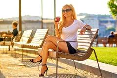 Junge Frau, die auf einer Bank mit einem Kaffee stationiert Stockfotos