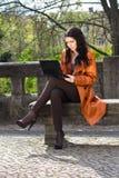Junge Frau, die auf einer Bank sitzt stockbild