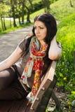 Junge Frau, die auf einer Bank sitzt lizenzfreie stockfotos