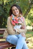 Junge Frau, die auf einer Bank sitzt Stockbilder