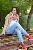 Junge Frau, die auf einer Bank sitzt Stockfoto