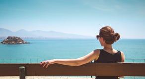 Junge Frau, die auf einer Bank sitzt und das Meer betrachtet Lizenzfreies Stockfoto