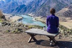 Junge Frau, die auf einer Bank sitzt und einen Fluss mit einer Schale betrachtet Stockfotografie