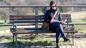Junge Frau, die auf einer Bank sitzt und etwas liest Petrovaradin-Festung, Novi Sad, Serbien stock video