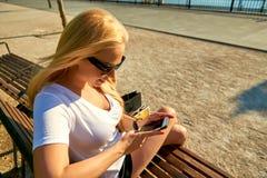 Junge Frau, die auf einer Bank stationiert und ihr Telefon verwendet Stockbilder