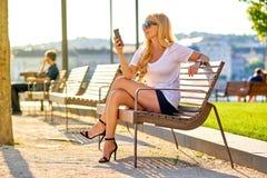 Junge Frau, die auf einer Bank stationiert und ihr Telefon verwendet Lizenzfreies Stockfoto