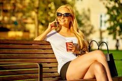 Junge Frau, die auf einer Bank stationiert und an ihrem Telefon spricht Stockfoto