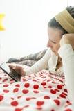Junge Frau, die auf einer Bettdecke betrachtet ihre digitale Tablette liegt lizenzfreie stockfotos