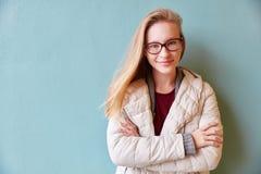Junge Frau, die auf einer blauen Wand sich lehnt Stockbilder