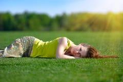 Junge Frau, die auf einer grünen Wiese liegt Lizenzfreie Stockfotos