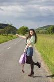 Junge Frau, die auf einer Landstraße trampt Lizenzfreie Stockfotos