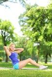 Junge Frau, die auf einer Matte in einem Park trainiert Lizenzfreie Stockbilder