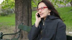 Junge Frau, die auf einer Parkbank sitzt stock video footage