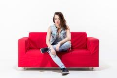 Junge Frau, die auf einer roten Couch sitzt Lizenzfreies Stockfoto
