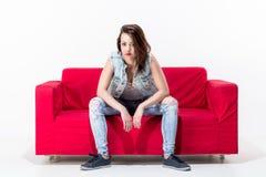 Junge Frau, die auf einer roten Couch sitzt Lizenzfreie Stockfotografie