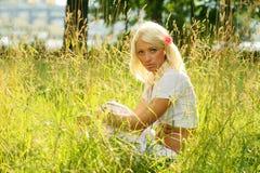 Junge Frau, die auf einer Sommerwiese sitzt Lizenzfreie Stockbilder