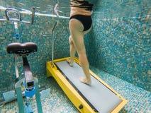 Junge Frau, die auf einer Unterwassertretmühle rüttelt stockfotografie