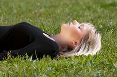 Junge Frau, die auf einer Wiese liegt Stockfotos