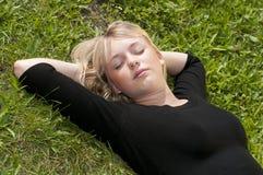 Junge Frau, die auf einer Wiese liegt Lizenzfreie Stockfotos