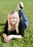 Junge Frau, die auf einer Wiese liegt Lizenzfreies Stockfoto