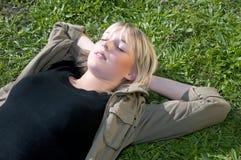 Junge Frau, die auf einer Wiese liegt Lizenzfreie Stockfotografie
