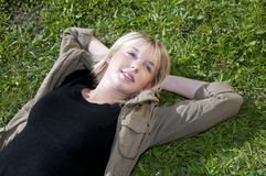 Junge Frau, die auf einer Wiese liegt Stockbild