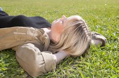 Junge Frau, die auf einer Wiese liegt Lizenzfreie Stockbilder
