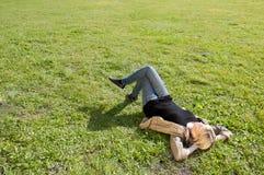 Junge Frau, die auf einer Wiese liegt Stockfotografie