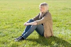 Junge Frau, die auf einer Wiese sitzt Stockfoto