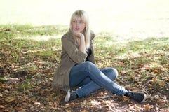 Junge Frau, die auf einer Wiese sitzt Stockbild