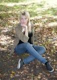 Junge Frau, die auf einer Wiese sitzt Stockbilder