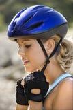 Junge Frau, die auf Fahrradsturzhelm sich setzt. Stockfotos