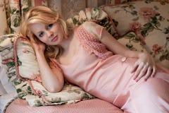 Junge Frau, die auf fantastischem Bett sich entspannt Stockfoto