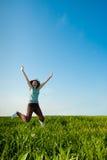 Junge Frau, die auf Feld springt Lizenzfreies Stockfoto