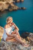 Junge Frau, die auf Felsen auf tropischem Strand ein Sonnenbad nimmt Stockbilder