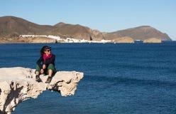 Junge Frau, die auf gemeißelter Felsenstruktur, Los Escullos, Spanien sitzt stockfotografie