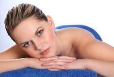 Junge Frau, die auf Gesundheitsbadekurort-Massagetabelle liegt Lizenzfreie Stockfotografie